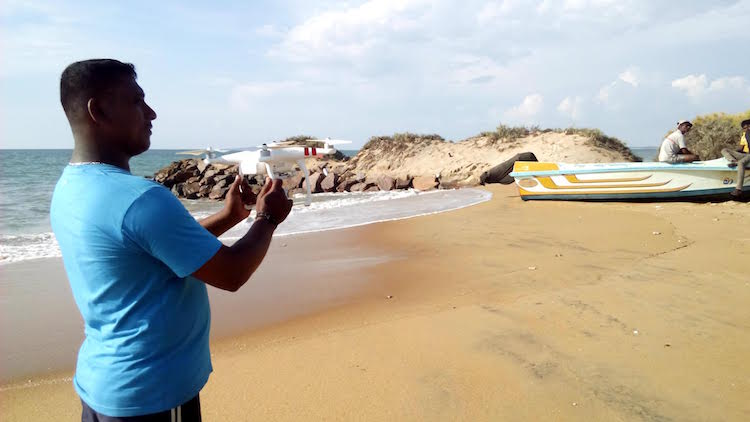 Photo: A conservationist holds a remote controlled drone at the Kalpitiya beach, Sri Lanka. The drone is used to study and protect Dugong, world's only vegetarian sea mammal. Credit: Stella Paul