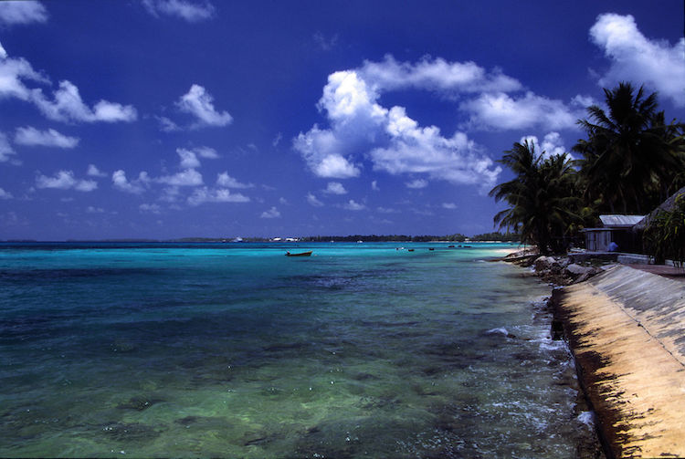 Photo: A beach at Funafuti atoll, Tuvalu, on a sunny day. Credit: Wikimedia Commons.