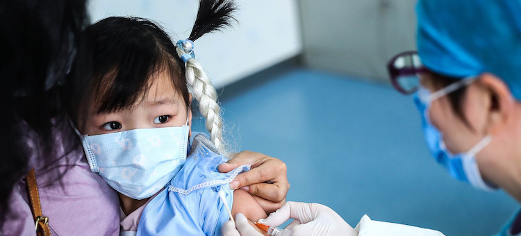 Photo: A three-year-old girl receives a vaccine shot at a community health centre in Beijing. Credit: UNICEF/Zhang Yuwe