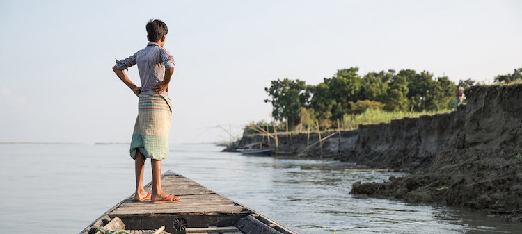 Photo: A boy watches the shore from a boat near Sirajganj, a community affected by severe erosion that has left many displaced. Sirajganj, Bangladesh. October 2016. Credit: IOM/Amanda Nero.