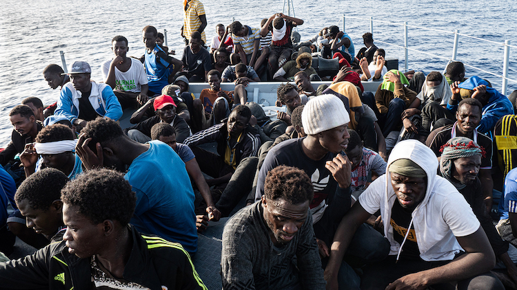Photo: Migrants on board a boat headed for Tripoli in July 2019. Critics say the EU should not be helping the Libyan Coast Guard to intercept and return people to a war-torn country where they face abuse and extortion. (Filippo Rossi/TNH)