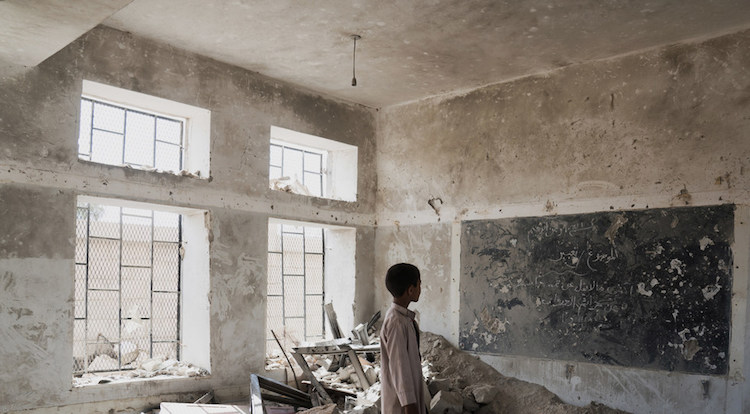 Photo: A student stands in the ruins of one of his former classrooms, which was destroyed in June 2015, at the Aal Okab school in Saada, Yemen. Students now attend lessons in UNICEF tents nearby. UNICEF/Clarke for UNOCHA.