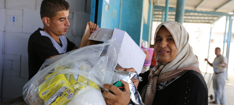 Photo: A Palestine refugee woman receives food assistance at the UNRWA Khan Younis Distribution Centre in Gaza. Credit: UNRWA | Tamer Hamam